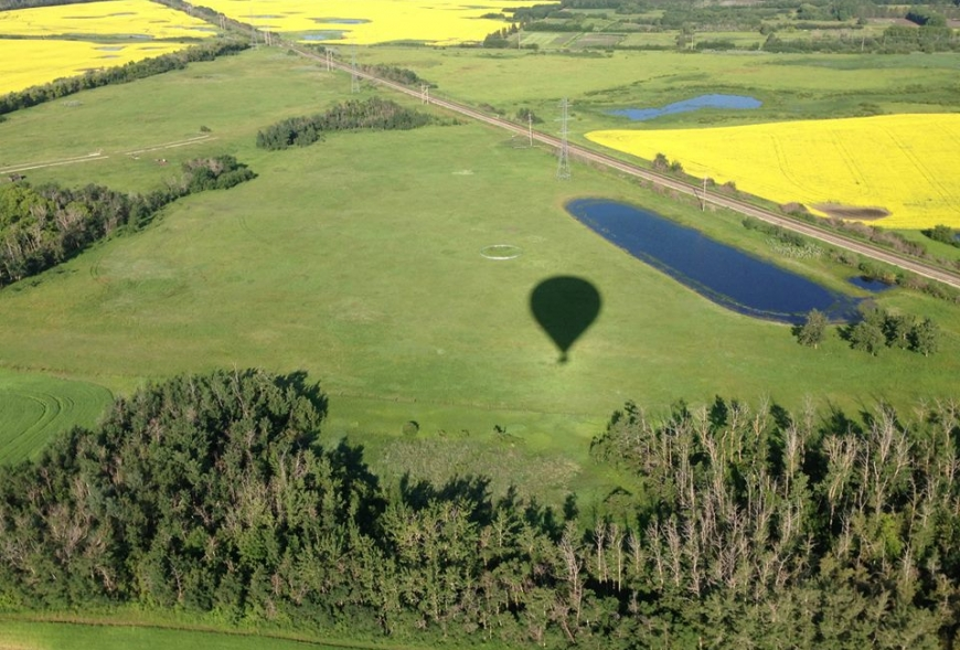 Picture of hot air balloon flying over field